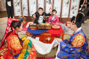 Pyebaek ceremony after wedding in Chinese culture, where dates and chestnuts are thrown in the bride's skirt by her in-laws to determine the number of kids she will have.