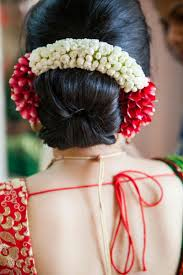 bridal hairstyle bun with red and white flowers