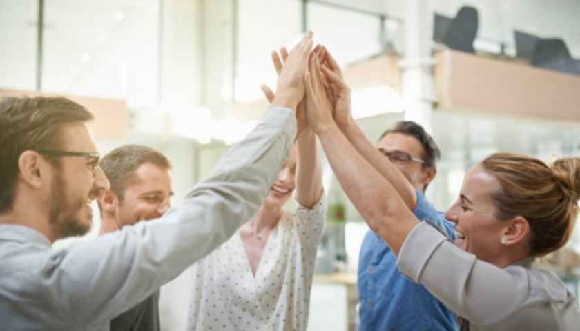 Co-workers sharing a group high-five in an office setting